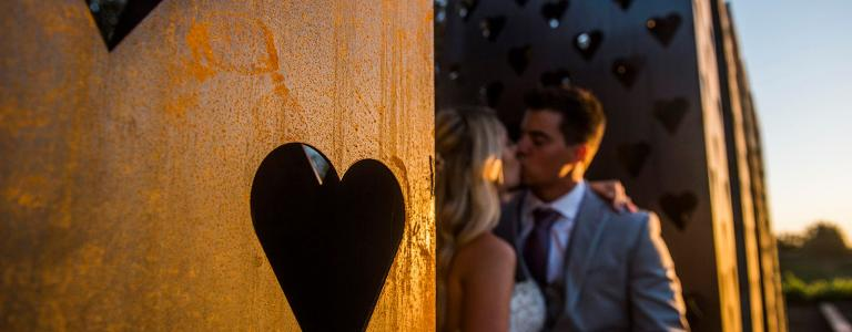 Bride and groom kissing by love sign