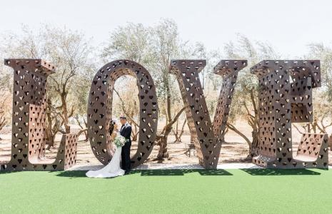 A couple standing in front of a large sculpture reading 'LOVE'